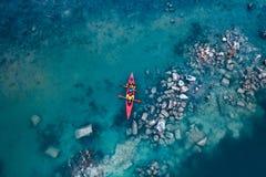 在一条红色小船的两个运动人浮游物在河 免版税库存照片