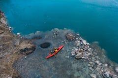 在一条红色小船的两个运动人浮游物在河 免版税库存图片