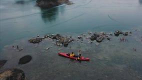 在一条红色小船的两个运动人浮游物在河 股票录像