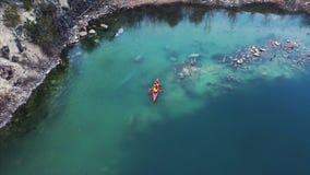 在一条红色小船的两个运动人浮游物在河 影视素材
