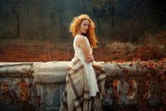 在一条红色毯子日出的红色头发女孩包裹的 库存照片