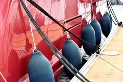 在一条红色游艇的身体的浮游物 免版税库存图片