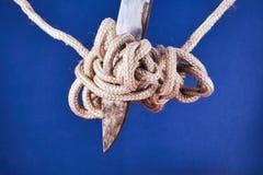 在一条绳索的一个被缠结的结与刀片 免版税库存照片