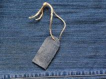 在一条绳索的时髦的空白的价牌在牛仔布背景为 库存图片