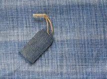 在一条绳索的空白的价牌在牛仔布背景seaso的 库存照片