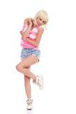 在一条腿的无忧无虑的白肤金发的少妇跳舞 库存照片