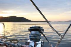 在一条航行的巡航游艇上的最基本的绞盘 从驾驶舱的看法在日落背景 安静和镇静早晨 库存图片