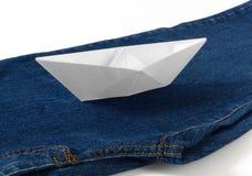 在蓝色牛仔裤的纸小船 免版税库存照片