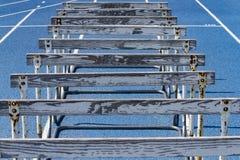 在一条蓝色高中轨道的木障碍 库存照片