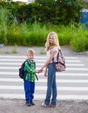 在一条行人交叉路附近的儿童立场 库存照片