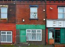 在一条街道上的下来奔跑露台的房子在有破旧的腐朽的五颜六色的被绘的墙壁的利兹和商店朝向与门户开放主义 免版税库存照片