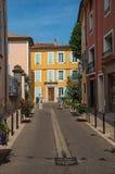 在一条街道上的两个人有五颜六色的房子的在历史桔子的市中心 免版税库存照片