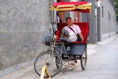 在一条街道上的中国人力车司机在Hutong在北京 免版税库存图片