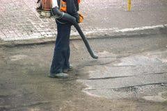 在一条街道上的工作者在秋天收集有吹叶机的叶子 库存图片