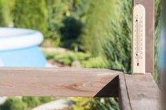 在一条街道上的木庭院温度计在乡间别墅里 免版税库存照片