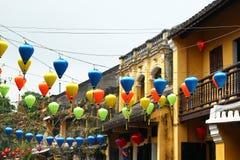 在一条街道上的看法在有黄色大厦、树和五颜六色的灯笼的老镇在导线 在泰特庆祝前的城市装饰 免版税库存图片