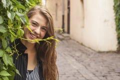 在一条街道上的年轻美丽的女孩在老镇 愉快 库存照片