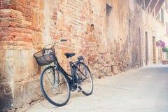 在一条街道上的黑葡萄酒自行车在托斯卡纳村庄,意大利 免版税图库摄影