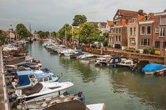 在一条街道的砖瓦房在运河和许多被停泊的小船旁边在多德雷赫特的一多云天 免版税库存图片