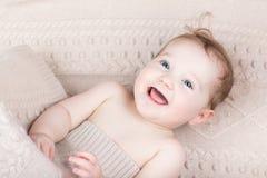 在一条被编织的毯子下的滑稽的笑的婴孩 免版税库存图片