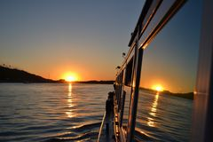 在一条观光的小船的窗口反映的日落 免版税图库摄影