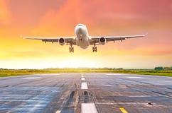 在一条跑道的大远程飞机飞行deperture着陆在明亮的红色日落期间的晚上 免版税图库摄影