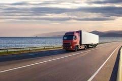 在一条路的卡车在海附近 免版税库存照片