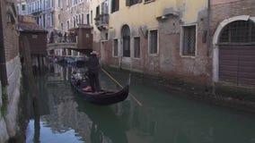 在一条运河的小桥梁在有长平底船、人和历史建筑的威尼斯 股票录像