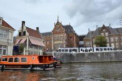在一条运河的旅游巡航小船在阿姆斯特丹 免版税库存图片