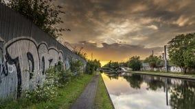 在一条运河的日落,有在前景的一街道画报道的waqll的 免版税库存图片
