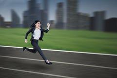 在一条连续轨道的女实业家奔跑 免版税图库摄影