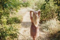 在一条道路的女孩后面在森林 免版税库存照片