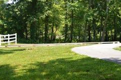 在一条道路的白色篱芭在一个低胸的绿色领域和绿色森林旁边 库存图片