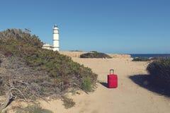 在一条道路的红色手提箱向在盖帽de ses Salines的灯塔 免版税库存图片