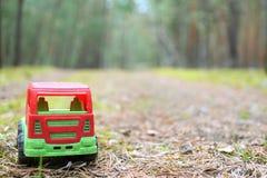在一条遮荫森林公路的玩具卡车 免版税库存图片