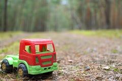在一条遮荫森林公路的玩具卡车 免版税库存照片