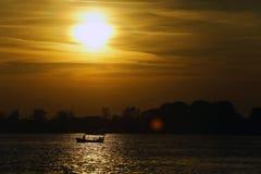 在一条镇静河的小船与反射在水的阳光的日落的 库存照片