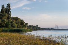 在一条镇静河的晴天有纸莎草的在夏天 新卡霍夫卡,乌克兰 在日落的高压输电线 库存照片