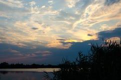 在一条镇静河的黄色和红色日落 库存照片