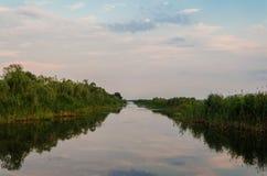 在一条镇静河的黄色和红色日落 图库摄影
