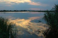 在一条镇静河的黄色和红色日落 免版税库存图片