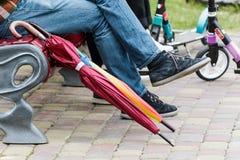 在一条长凳的伞在城市 免版税库存图片