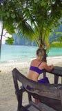 在一条长凳的少妇选址在海滩 库存照片
