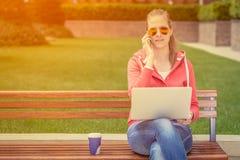 在一条长凳的年轻女性开会在公园,打一次电话与 免版税图库摄影