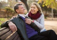 在一条长凳的年长夫妇在公园在秋天天 库存图片