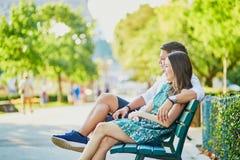 在一条长凳的愉快的约会夫妇在一个巴黎人公园 免版税库存图片