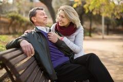 在一条长凳的愉快的年长夫妇在公园在秋天天 免版税库存图片