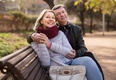 在一条长凳的愉快的年长夫妇在公园 免版税库存照片