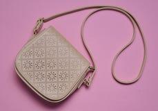 在一条长的皮带的米黄皮包在桃红色淡色背景 Women& x27; s辅助部件 顶视图 免版税库存图片