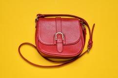 在一条长的皮带的红色皮包在黄色背景 妇女& x27; s辅助部件 免版税库存照片